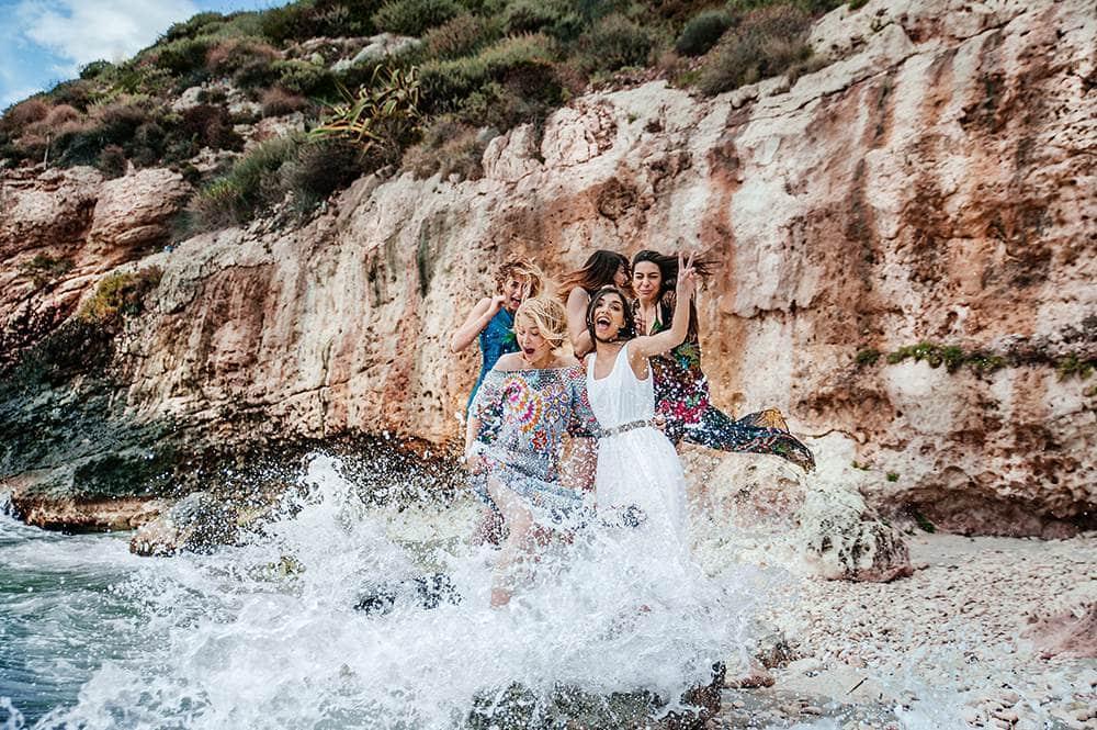 девушки в брызгах морской волны на острове