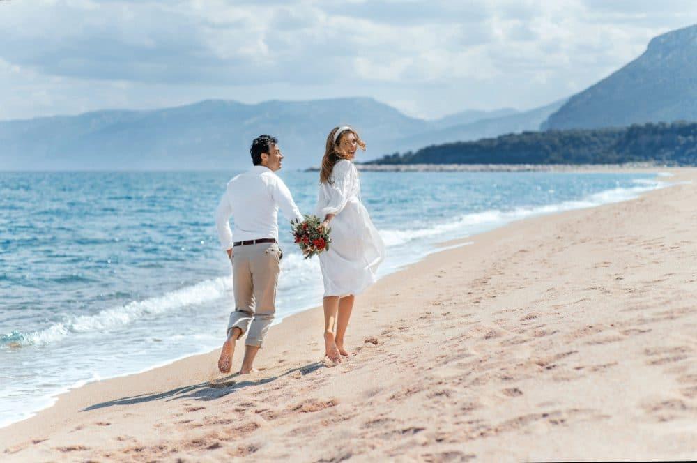 жених и невеста на пляже с букетом
