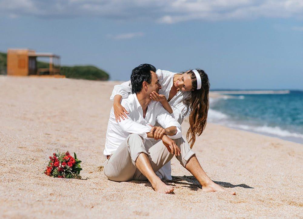 молодожены с букетом невесты на пляже