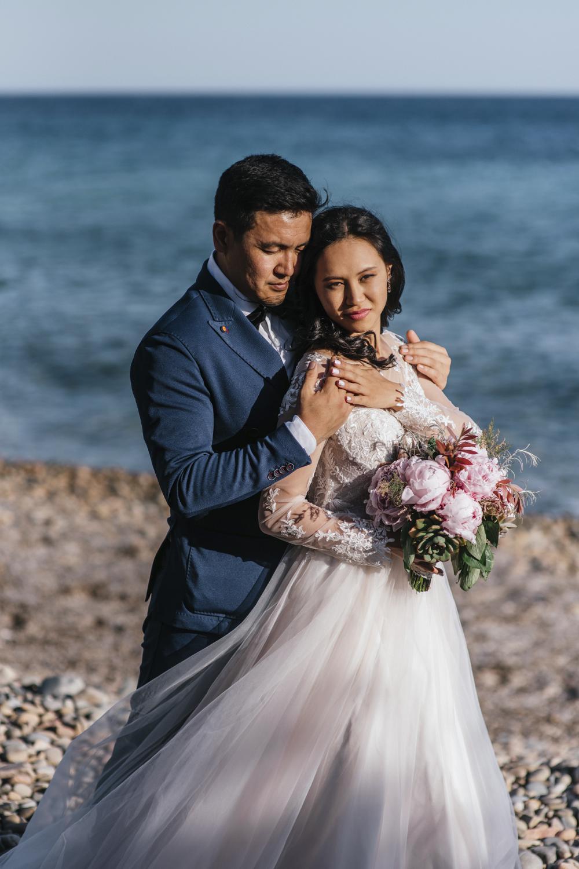 жених и невеста на пляже во время свадебной фотосессии