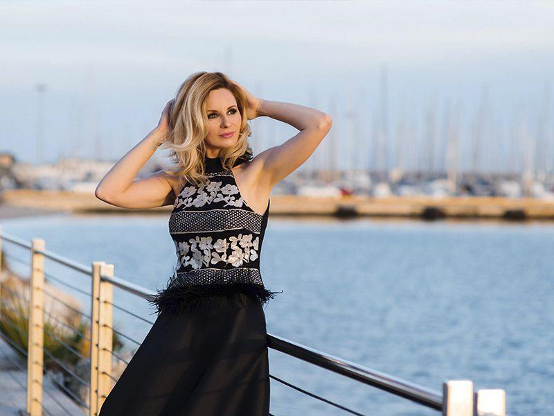 Красивая женщина в вечернем платье на променаде в Кальяри